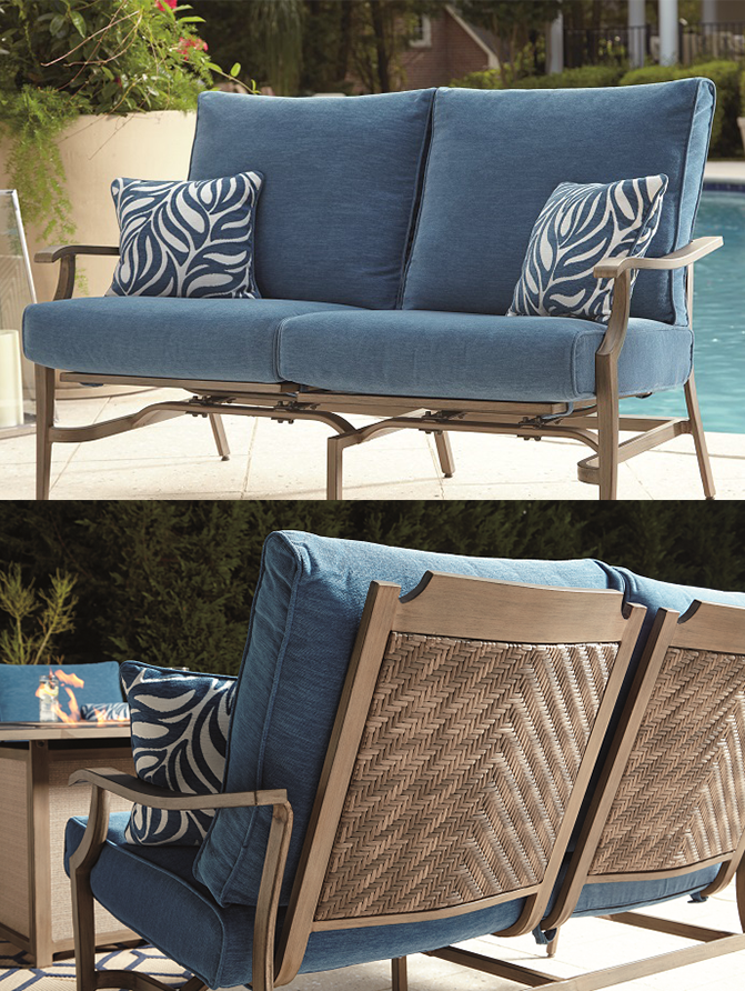 Blue and cushioned outdoor love seat with 2 pillows with a leaf design on a patio with a pool in the background.