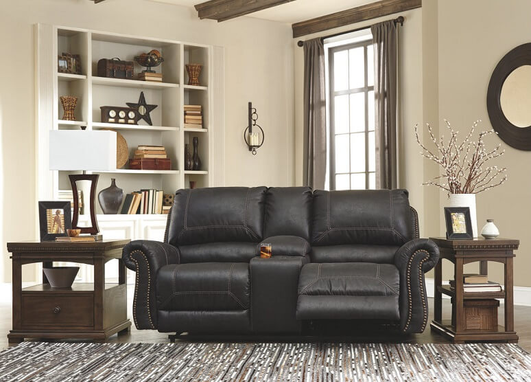 Black leather reclining sofa with upholders in a living room with two end tables next to the sofa.