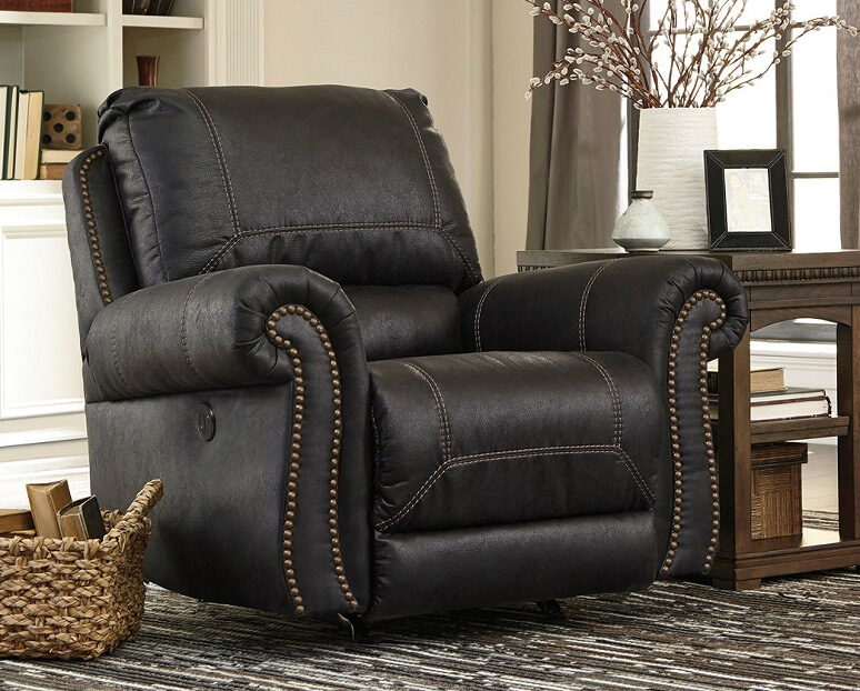 Blackish brown reclining chair in a living room with a rug and basket on the ground.