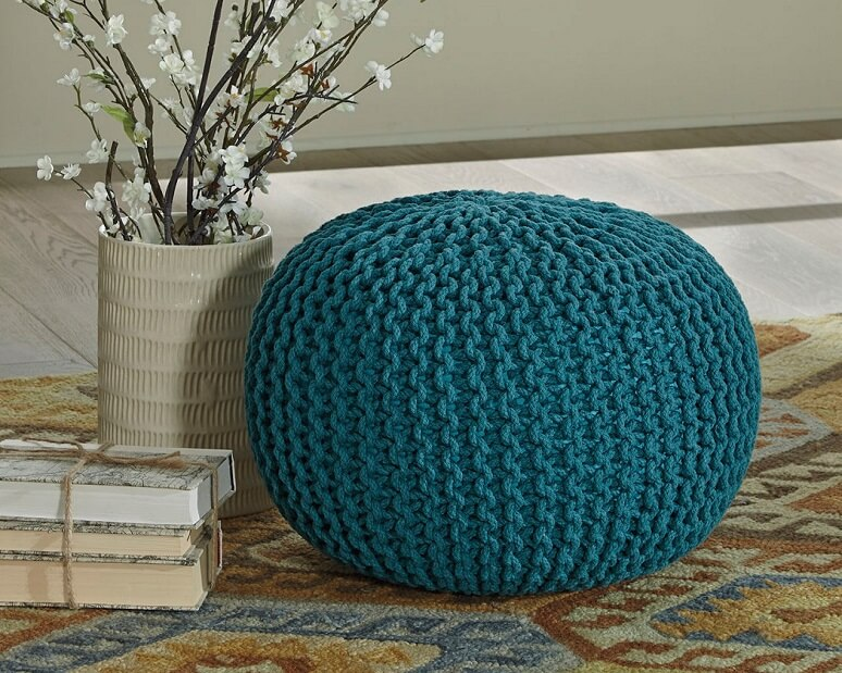 Blue fabric pouf on a rug next to a vase with flowers in it.