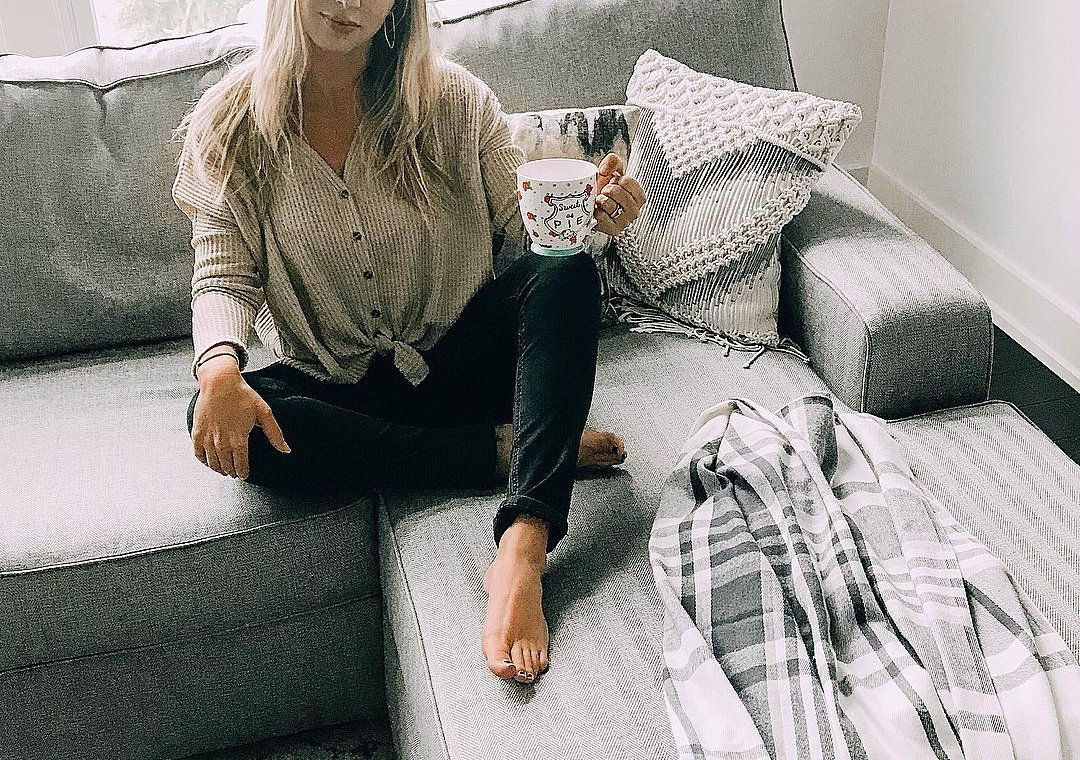 woman sitting on gray couch with coffee