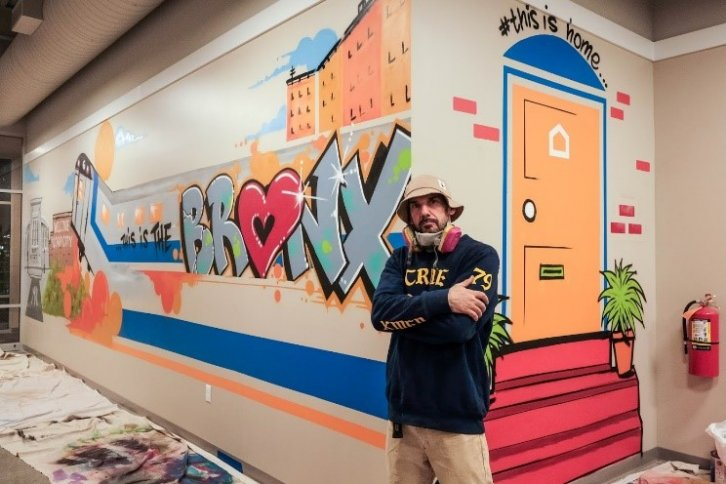 Man poses with mural.