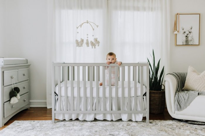Baby standing in crib.